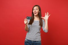 Portrait of curious young woman in striped clothes looking up, holding credit card, showing palm isolated on bright red stock photo