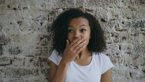 Portrait of curly african american teenager girl actively surprising and wondering on brick wall background stock photos