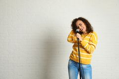 Portrait of curly African-American woman singing in microphone near brick wall. Space for text stock images