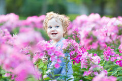 Portrait of curly baby girl with blue eyes in a field Royalty Free Stock Photography