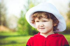 Portrait of curly baby in white hat. Royalty Free Stock Images