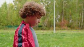Portrait curly boy walking in green park. Dolly shot teenager boy walking in park on trees landscape. Cute boy looking. To camera on park walk stock video footage