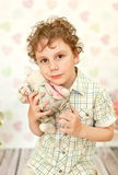 Portrait of curly brown-eyed boy in a light beige dress Stock Photo