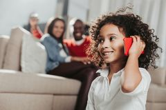 Enjoyed kid chatting by smartphone indoors Royalty Free Stock Photo