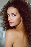 Portrait of a curly girl with blue eyes with bared shoulders sitting back. And looking at the camera Stock Photos