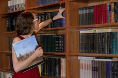 College girl hiding behind book. Royalty Free Stock Photography