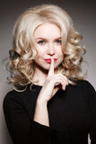 Portrait of curly gorgeous blonde girl in black blouse holding finger on lips and gesturing sign of silence. Posing and looking at Stock Photography