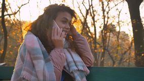 Portrait of curly-haired caucasian girl sitting on bench and talking on cellphone attentively in autumnal park. Portrait of curly-haired caucasian girl sitting stock photo