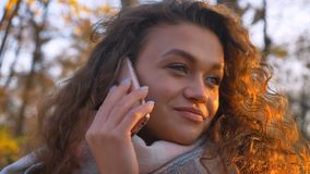 Portrait of curly-haired caucasian girl talking on cellphone pleasantly in autumnal park. Portrait of curly-haired caucasian girl talking on cellphone royalty free stock photo