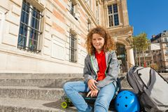 Teen sitting outdoors with skateboard and helmet. Portrait of curly-haired teenage boy sitting outdoors on the staircase with backpack, skateboard and helmet Stock Photo