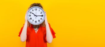 Woman in dress with clocks. Portrait of curly-haired woman in red dress and eyeglasses isolated on orange background hiding her face behing big clocks time limit Stock Photography