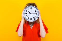 Woman in dress with clocks. Portrait of curly-haired woman in red dress and eyeglasses isolated on orange background hiding her face behing big clocks time limit Royalty Free Stock Images