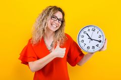 Woman in dress with clocks. Portrait of curly-haired woman in red dress and eyeglasses isolated on orange background holding clocks and showing her thumb up on Royalty Free Stock Photography