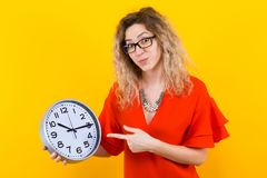 Woman in dress with clocks. Portrait of curly-haired woman in red dress and eyeglasses isolated on orange background holding clocks and showing on them time Royalty Free Stock Images