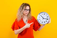 Woman in dress with clocks. Portrait of curly-haired woman in red dress and eyeglasses isolated on orange background holding clocks and showing on them time Royalty Free Stock Image