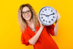Woman in dress with clocks. Portrait of curly-haired woman in red dress and eyeglasses isolated on orange background holding clocks time limit punctuality Royalty Free Stock Photos