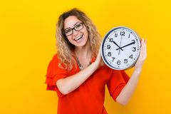 Woman in dress with clocks. Portrait of curly-haired woman in red dress and eyeglasses isolated on orange background holding clocks time limit punctuality Stock Photos