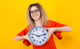 Woman in dress with clocks. Portrait of curly-haired woman in red dress and eyeglasses isolated on orange background holding clocks time limit punctuality Royalty Free Stock Image