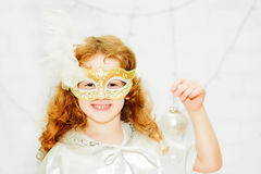 Portrait of a curly little girl in venetian mask on a light back Royalty Free Stock Image
