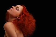 Portrait of the curly red-haired girl. On a black background royalty free stock photography