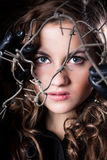 Portrait of curly woman with blue eyes posing behind barbed wire Royalty Free Stock Photos