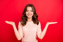 Portrait of curly woman hold invisible object or product on rais. Ed up palms on two hands isolated on vivid red background with copy space for text royalty free stock photography