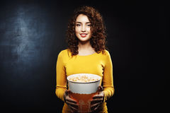 Portrait of curly woman holding popcorn bucket looking straight. Portrait of curly woman, cinema visitor posing with popcorn after seeing nice movie at theatre Royalty Free Stock Photo