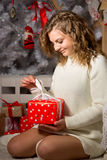 Portrait of curly woman unpacking red Christmas gift box Stock Photo