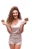 Portrait of curly young woman eating a chocolate bar. Against a white background Stock Photography