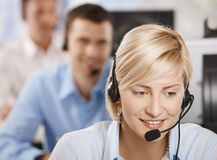 Portrait of customer service operator. Portrait of young customer service operator talking on headset, smiling Stock Photos