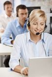 Portrait of customer service operator. Portrait of young customer service operator talking on headset, smiling Stock Photos
