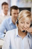 Portrait of customer service operator. Portrait of young customer service operator talking on headset, smiling Royalty Free Stock Photography