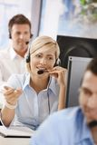 Portrait of customer service operator. Portrait of young customer service operator talking on headset, smiling Stock Images