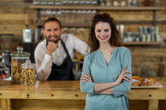 Portrait of customer standing with arms crossed with waiter in background. At caf Stock Photos