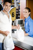 Portrait of a customer and supermarket checkout assistant Stock Image