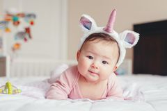 Cute adorable Asian mixed race smiling baby girl four months old lying on tummy on bed stock image