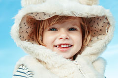 Portrait of cute adorable beautiful funny smiling laughing white blonde Caucasian child kid baby girl with blue eyes in fur coat Stock Photo