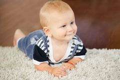 Portrait of cute adorable blond Caucasian smiling baby boy with blue eyes lying on floor in kids children room. Looking away royalty free stock photos