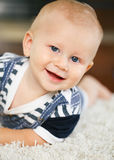 Portrait of cute adorable blond Caucasian smiling baby boy with blue eyes lying on floor in kids children room. Looking in camera royalty free stock photos