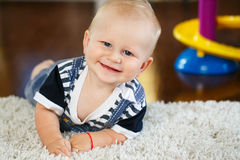 Portrait of cute adorable blond Caucasian smiling baby boy with blue eyes lying on floor in kids children room. Looking in camera stock image