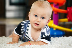 Portrait of cute adorable blond Caucasian smiling baby boy with blue eyes lying on floor in kids children room. Looking in camera stock photos
