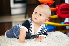 Portrait of cute adorable blond Caucasian smiling baby boy with blue eyes lying on floor in kids children room. Looking up royalty free stock photos