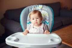 Caucasian child girl sitting in high chair ready to eat. Portrait of cute adorable blonde Caucasian child girl sitting in high chair ready to eat. Everyday royalty free stock image