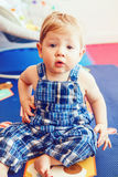 Portrait of cute adorable blonde Caucasian smiling baby boy with brown eyes in blue romper sitting on floor in kids room Royalty Free Stock Images