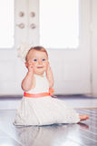Portrait of cute adorable blonde Caucasian smiling baby child girl with blue eyes in white dress with red bow sitting on floor ind Royalty Free Stock Photos