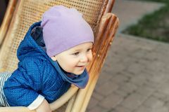 Portrait of cute adorable caucasian baby boy having fun sitting in  wooden rattan rocking chair on house terrace backyard outdoors stock photos