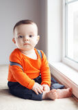 Portrait of cute adorable Caucasian baby boy sitting on windowsi Stock Image