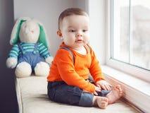 Portrait of cute adorable Caucasian baby boy sitting on windowsi Stock Photos