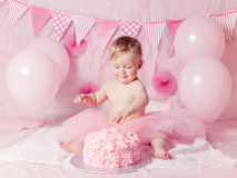 Portrait of cute adorable Caucasian baby girl with blue eyes in pink tutu skirt celebrating her first birthday with gourmet cake. And balloons looking away Royalty Free Stock Image