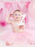 Portrait of cute adorable Caucasian baby girl with blue eyes in pink tutu skirt celebrating her first birthday with gourmet cake. And balloons looking away Stock Photography